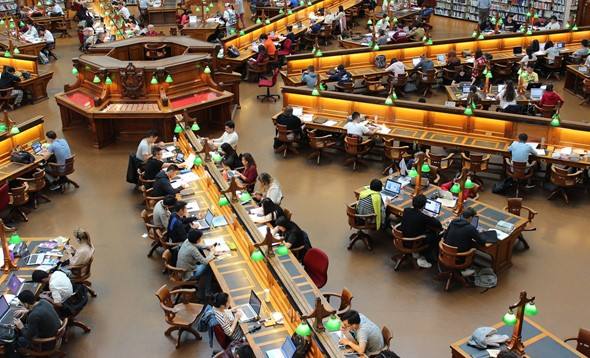 Old-style library filled with people sat at desks poring over books