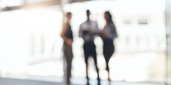 Blurred image of three professionals, one mand and two women, in office clothes standing up